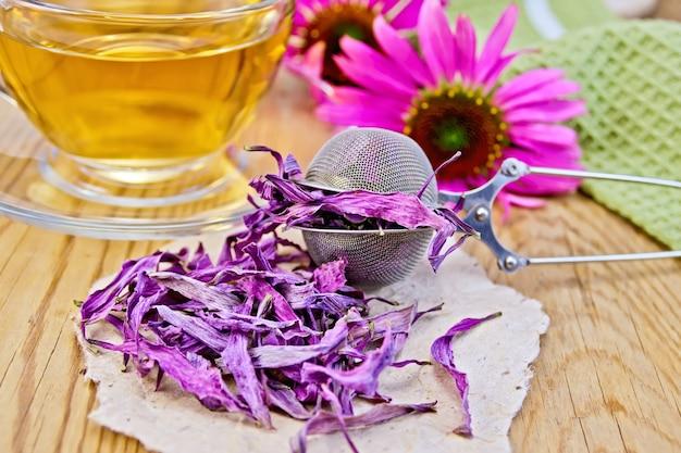 Echinacea seca em uma peneira de metal e papel, flores frescas de echinacea em um fundo de tábuas de madeira