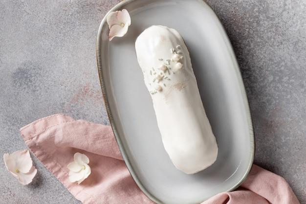 Eclair de chocolate branco em prato de cerâmica sobremesa francesa