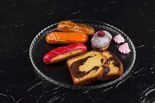 Eclair de morango com muffin de chocolate e fatias de torta.