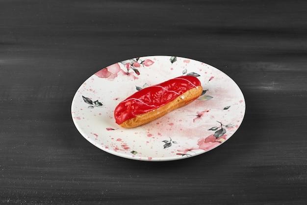 Eclair de morango em uma placa de cerâmica branca.