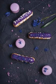 Eclair roxo mirtilo com macaroons em fundo preto texturizado