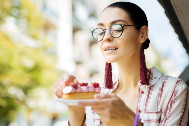 Éclairs amorosos. mulher alegre e relaxada apreciando a deliciosa sobremesa de framboesa e sorrindo enquanto olha gentilmente para ela