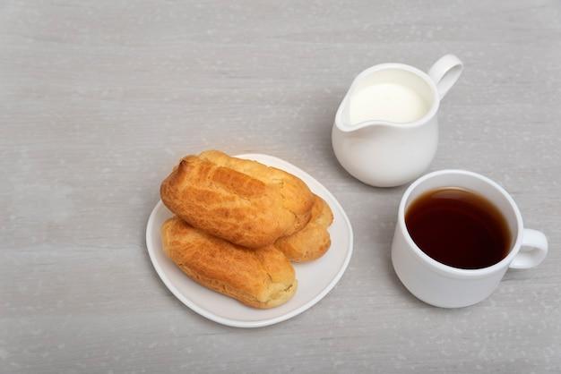 Éclairs caseiros, café e leite. éclairs franceses tradicionais. profiteroles em pires. superfície cinzenta.
