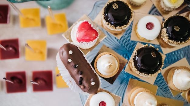 Eclairs cobertos com esmalte de chocolate servidos em prato de vidro