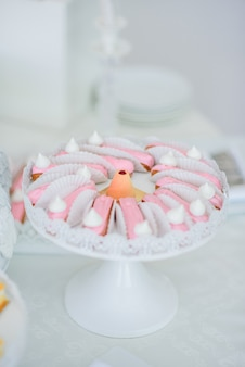 Eclairs cobertos com esmalte rosa servidos em prato branco redondo