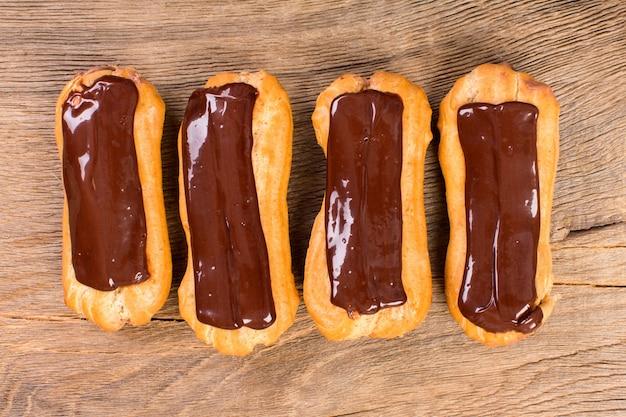 Éclairs com cobertura de chocolate no fundo de madeira. sobremesa tradicional francesa.