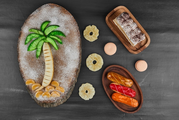 Éclairs com composição de frutas e fatia de tiramisu.