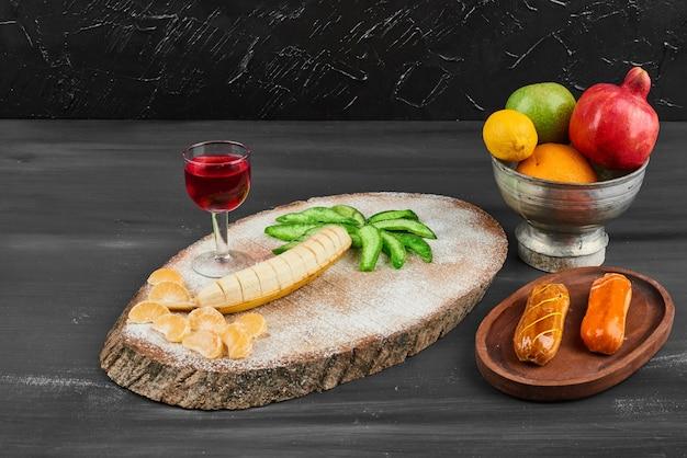Éclairs com composição de frutas e uma taça de vinho.