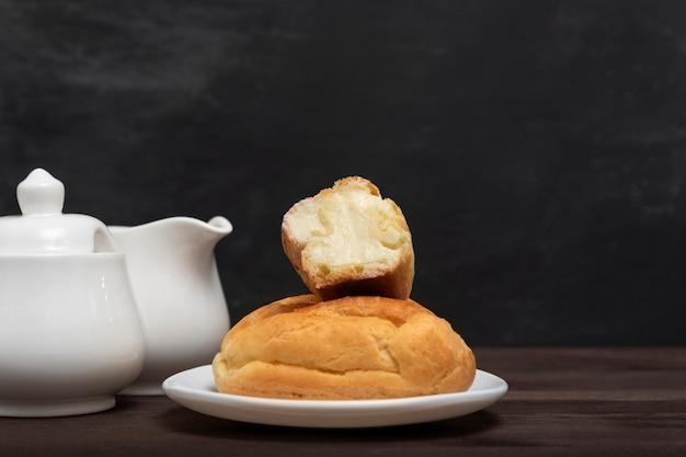 Éclairs com creme de manteiga no prato de servir. cozinhar para o chá. sobremesa francesa tradicional.