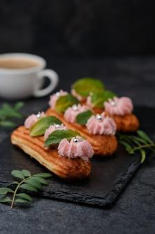 Éclairs com creme rosa, decorados com folhas de hortelã. sobremesa em um prato de ardósia preta. bolos e café expresso em um fundo escuro.
