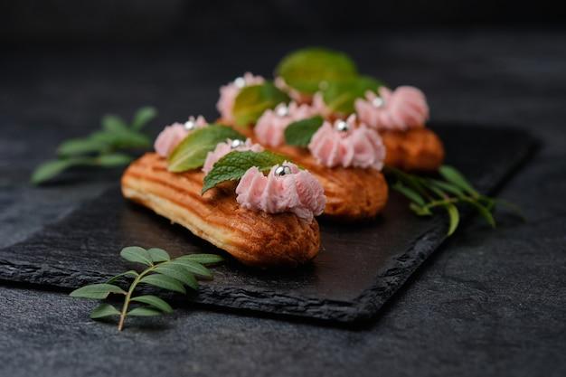 Éclairs com creme rosa, decorados com folhas de hortelã. sobremesa em um prato de ardósia preta. bolos em um fundo escuro.