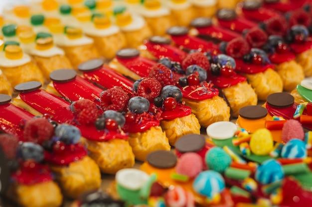 Éclairs com frutas vermelhas. éclairs doces deliciosos decorados com frutas vermelhas e colocados ao lado de éclairs doces doces