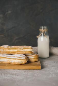 Eclairs cozidos na tábua de madeira com garrafa de leite