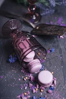 Eclairs cremoso-de-rosa e roxos em pano de fundo texturizado ardósia preto