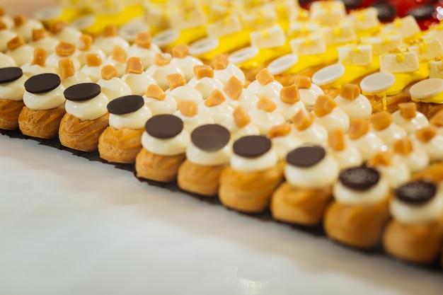 Éclairs de caramelo. deliciosos éclairs populares com pedaços de caramelo e fatias de chocolate amargo no topo