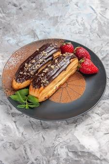 Eclairs de chocolate deliciosos com morangos em bolo de mesa leve e biscoitos de sobremesa