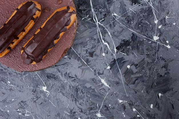 Éclairs de chocolate doces deliciosos colocados em um pedaço de madeira.