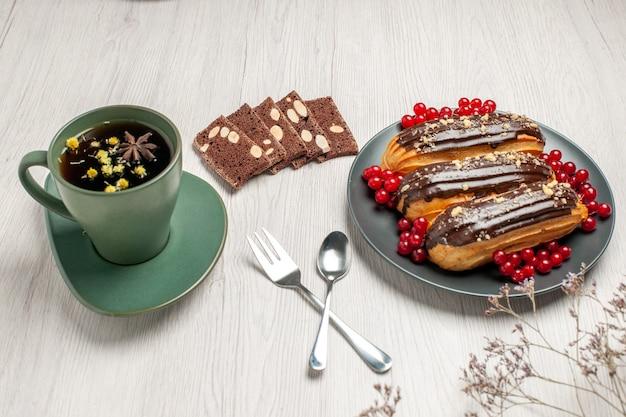 Éclairs de chocolate e groselha no prato cinza biscoitos de amendoim uma xícara de chá, colher e um garfo em vetor diagonal na mesa de madeira branca.
