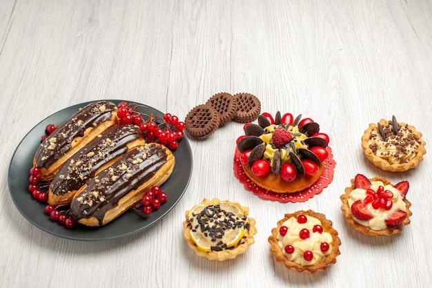 Éclairs de chocolate e groselhas no prato cinza, biscoitos e bolo de frutas vermelhas na mesa de madeira branca com espaço de cópia.