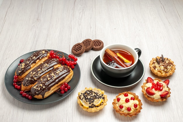 Éclairs de chocolate e groselhas no prato cinza, biscoitos e chá de canela com limão na mesa de madeira