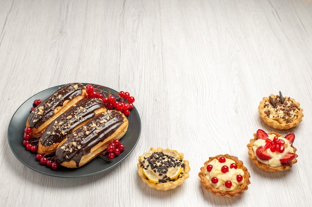 Éclairs de chocolate e groselhas no prato cinza e quatro tortas na mesa de madeira branca.