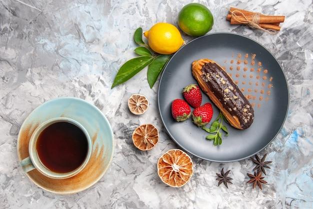 Éclairs de chocolate saborosos com uma xícara de chá em um biscoito de bolo de sobremesa leve