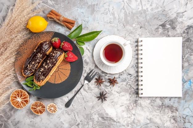 Éclairs de chocolate saborosos com uma xícara de chá em um biscoito de sobremesa de bolo de bolinho branco