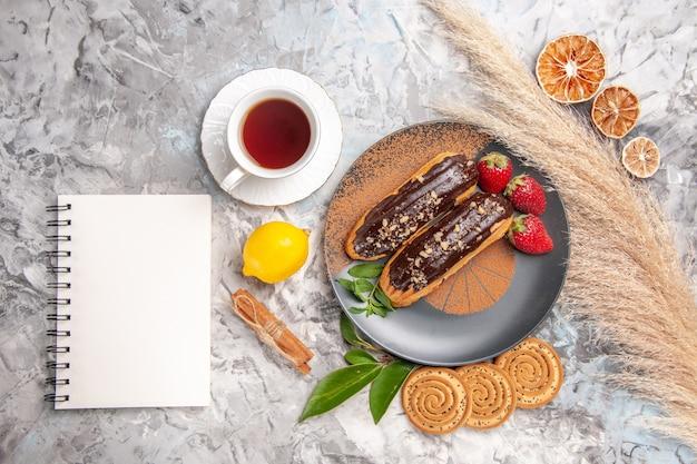 Éclairs de chocolate saborosos com uma xícara de chá no bolo branco e biscoito de sobremesa