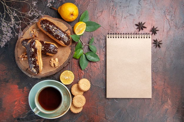 Éclairs de chocolate saborosos com uma xícara de chá no chão escuro e bolo doce de sobremesa