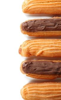 Éclairs deliciosos com chocolate em uma fileira em branco