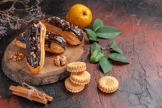 Éclairs deliciosos de chocolate com biscoitos em fundo escuro.