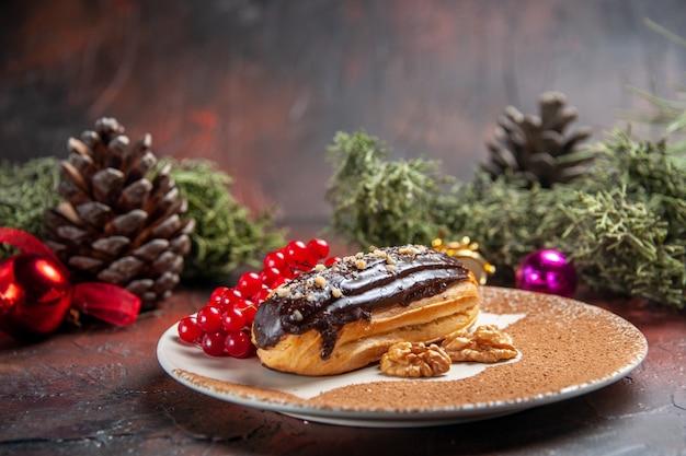 Éclairs deliciosos de chocolate com frutas vermelhas em fundo escuro de vista frontal