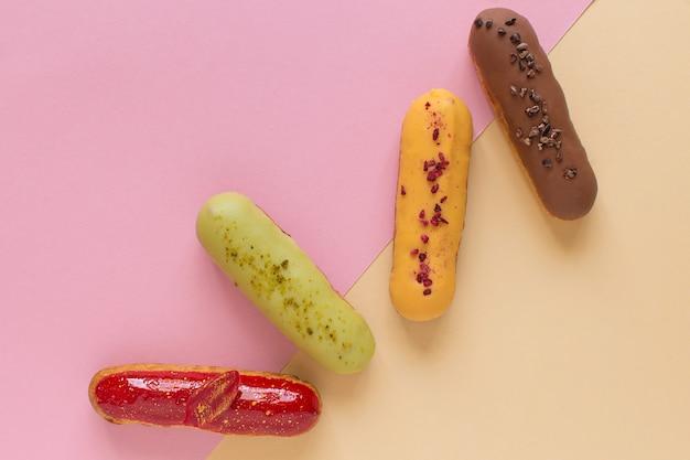 Éclairs em um fundo mínimo. natureza morta, olá, humor para sobremesa. sobremesa francesa tradicional com glacê colorido. cozimento de conceito, receitas de livro de receitas, banner de padaria, anúncio de café.