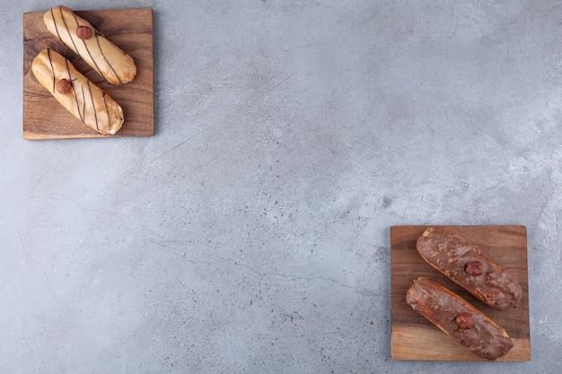 Éclairs franceses tradicionais com chocolate colocados na placa de madeira.