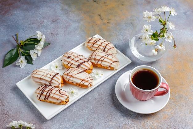 Éclairs ou profiteroles com chocolate preto e chocolate branco com creme dentro, sobremesa francesa tradicional.