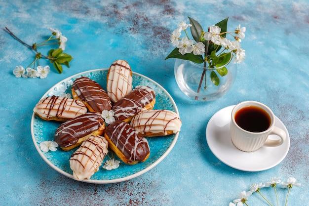 Eclairs ou profiteroles com chocolate preto e chocolate branco com creme dentro