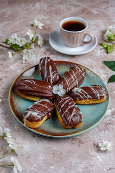 Eclairs ou profiteroles com chocolate preto e chocolate branco com creme para dentro, sobremesa francesa tradicional. vista superior.