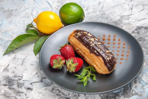 Eclairs saborosos de chocolate com morangos em um biscoito de bolo de sobremesa de mesa clara