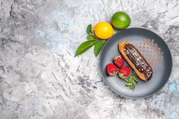 Eclairs saborosos de chocolate com morangos em um biscoito de bolo de sobremesa leve