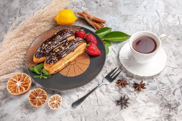 Eclairs saborosos de chocolate com morangos em um biscoito de sobremesa de bolo branco