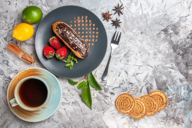 Eclairs saborosos de chocolate com uma xícara de chá no bolo de sobremesa de biscoito leve