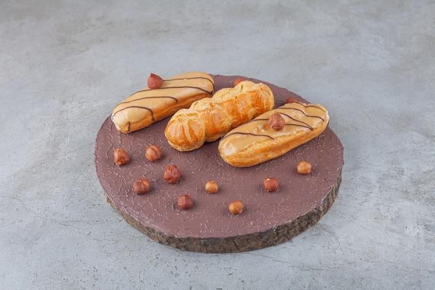 Éclairs simples tradicionais com avelãs colocados sobre uma peça de madeira. Foto Premium