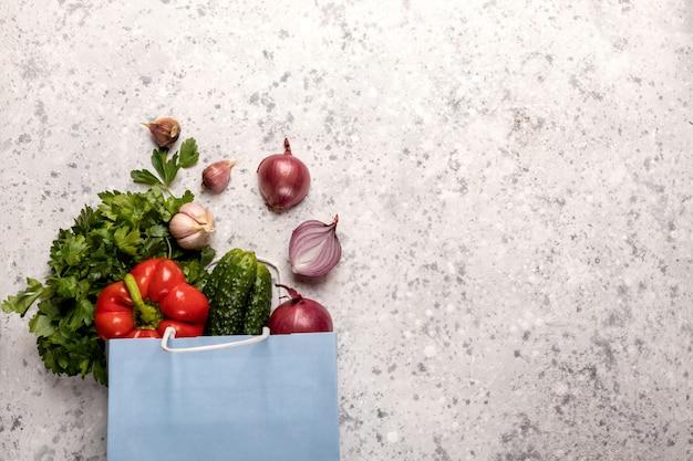 Eco amigável. ofício de papel pacote azul com legumes