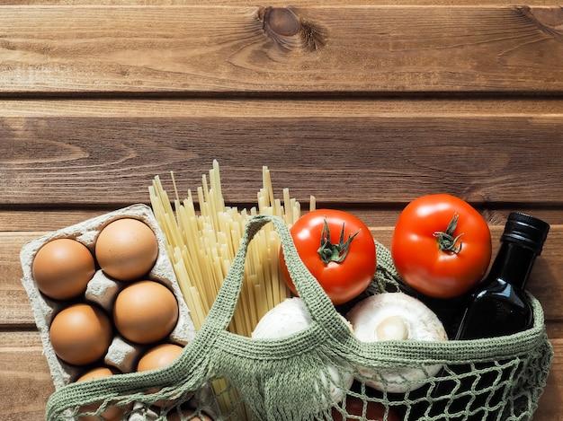 Eco amigável saco de compras reutilizável cheio de ovos, massas, tomate, cogumelos e óleo em fundo de madeira.