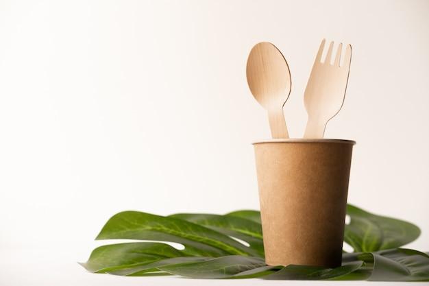 Eco amigável utensílios de cozinha descartáveis em fundo branco. garfos de madeira e colheres em copo de papel. ecologia, conceito de desperdício zero. vista do topo. configuração plana