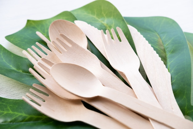 Eco amigável utensílios de cozinha descartáveis na superfície branca. garfos e colheres de pau. ecologia, conceito de desperdício zero. vista do topo. configuração plana. copyspace