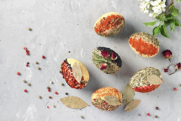 Eco-design de ovos de páscoa com várias especiarias e cereais, sem corantes e conservantes em um fundo cinza de concreto, vista de cima