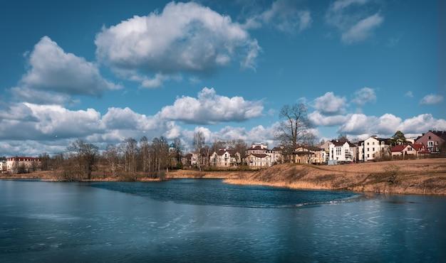 Eco-friendly cottage aldeia na margem do lago. paisagem brilhante primavera com casas perto de um lago congelado.