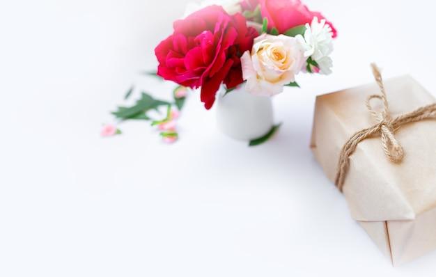 Eco friendly papel pardo embrulhado presente caixa de presente decorada com rosas e outras flores em fundo branco, férias românticas apresenta conceito, cópia espaço. dia dos namorados ou conceito do dia da mulher