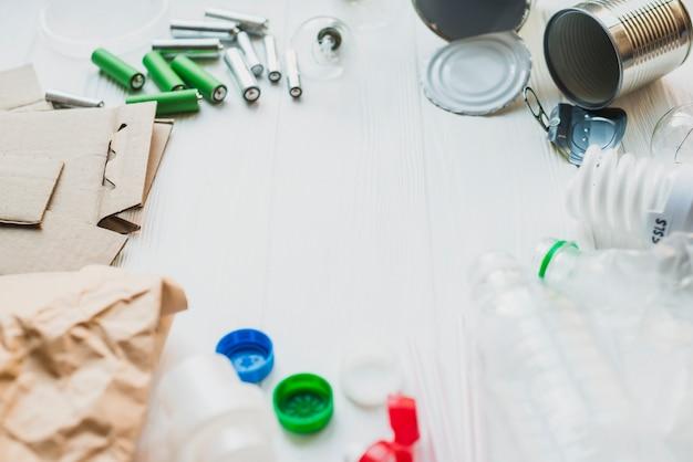 Eco reciclar ícone no plano de fundo texturizado de madeira com itens de reciclagem